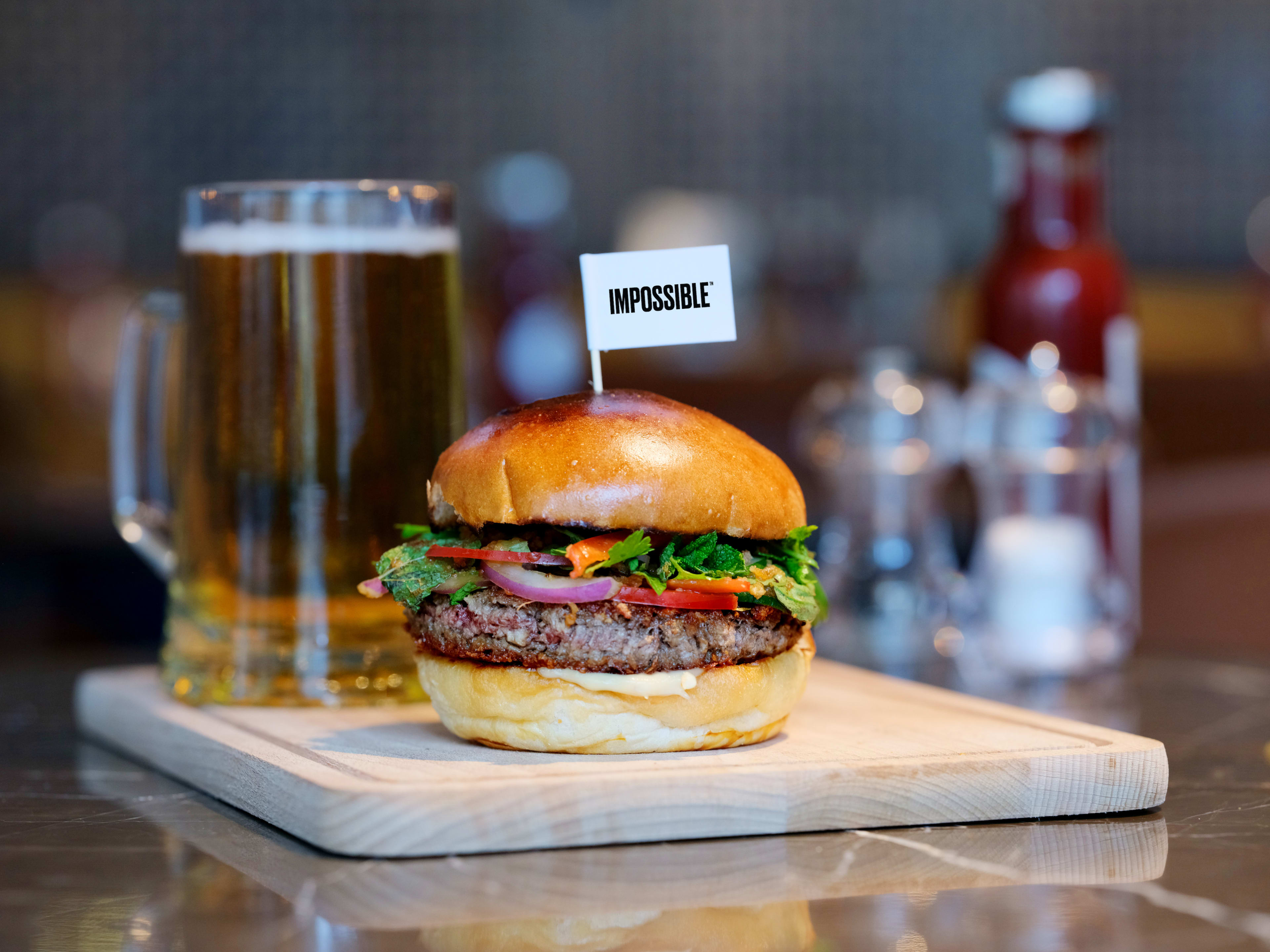 Impossible Burger with toothpick flag with a beer stein and ketchup and salt and pepper