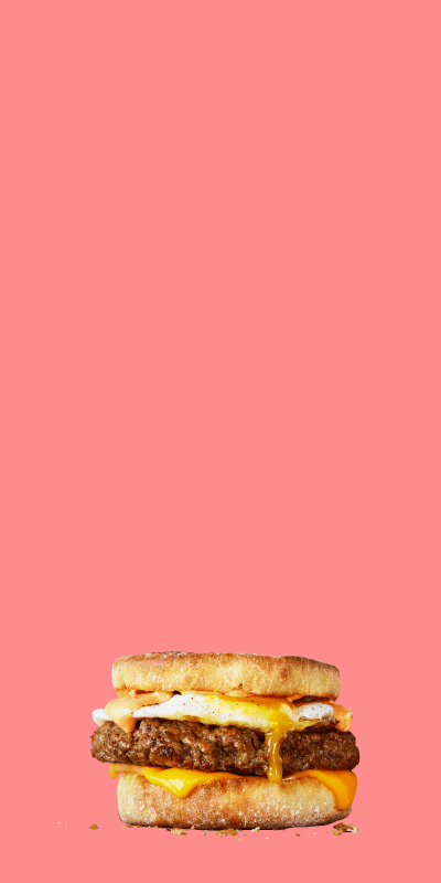 Stack of delicious food items made with Impossible Sausage made from plants including a breakfast sandwich, omelet, and breakfast burrito -- on on a pink background