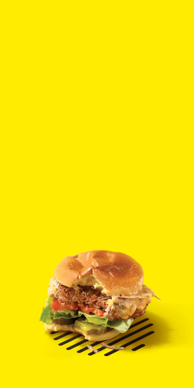 Impossible Burger with a bite taken out of it on grill marks yellow background