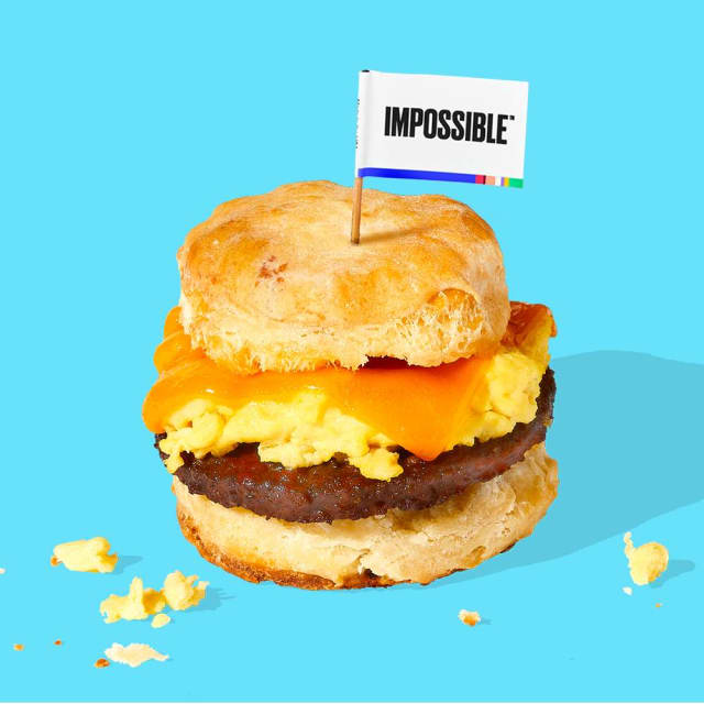 Impossible™ Sausage Made From Plants Biscuit Sandwich with eggs and an Impossible™ flag on top.