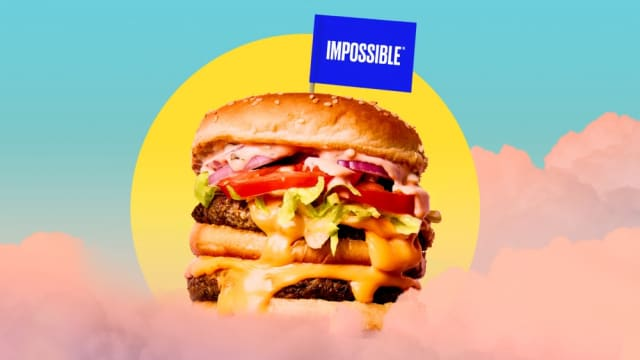 Impossible™ Burger with melty cheese and toppings, plus an Impossible flag, floating in the sky with the sun in the background.
