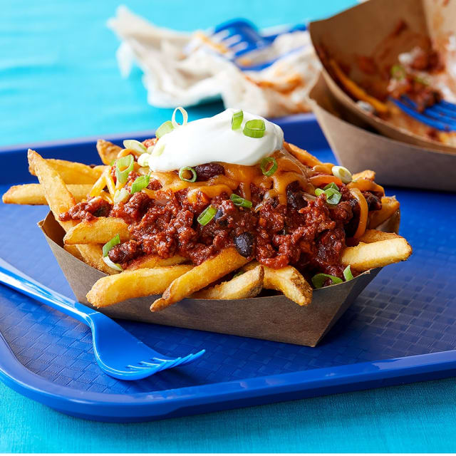 Impossible™ Chili Cheese Fries topped with green onions and sour cream