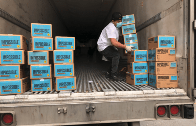 Man loading boxed of Impossible Food and Impossible Burger from truck Plant Based Meat Alternatives