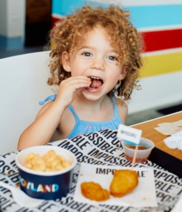 young girl eating Impossible chicken nuggets on a tray with fries and ketchup
