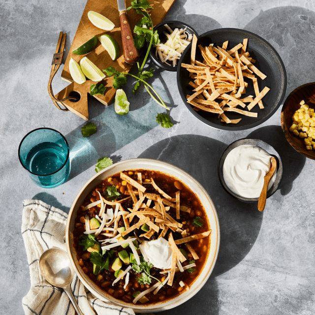 Impossible™ Tortilla Soup made in a Slow Cooker with black beans, corn, and a spicy broth, topped with tortillas strips, cilantro, lime and creamy avocado and sour cream.
