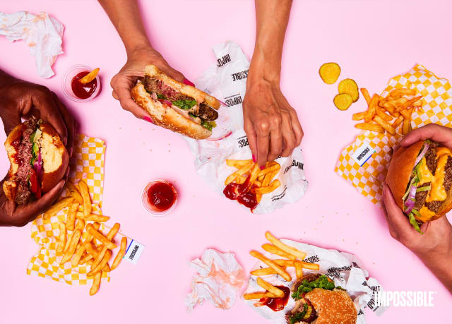 A group of millennials eating Impossible Burger and Fries