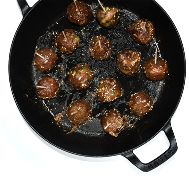 Miso-Sesame-Glazed Impossible™ Meatballs in a cast iron skillet, coated in gingery miso sauce and sesame seeds.