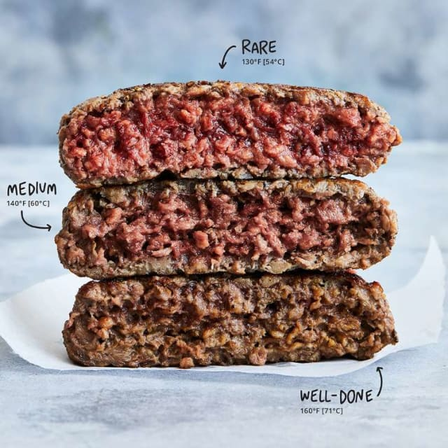Impossible Burger patties on a flattop grill, sizzling