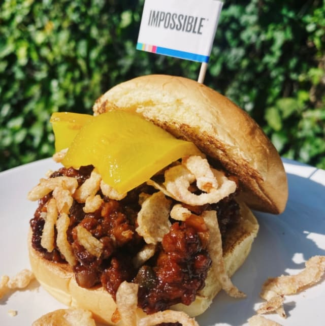 Impossible Sloppy Joe made with Impossible™ Burger, piled high with fried onions, tangy sweet and savory sauce, and melty cheese.