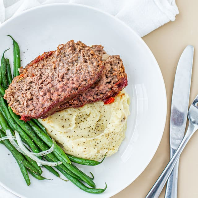 BBQ Impossible Burger with mashed potatoes and green beans on white plate