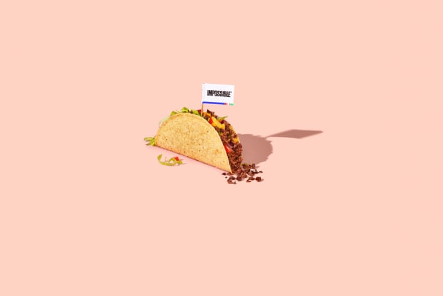 Taco filled with Impossible™ Burger, melty cheese, lettuce, tomatoes, and a flag saying Impossible™