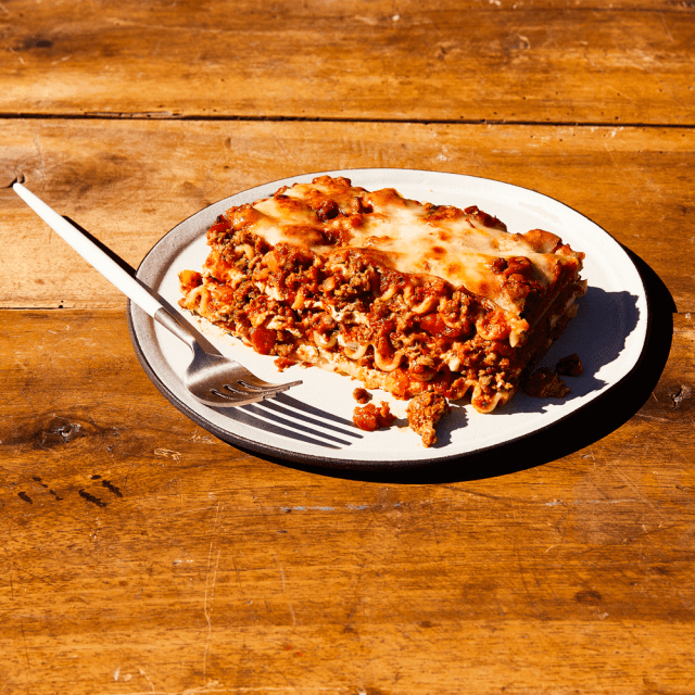 Slice of Impossible™ Lasagna made in a Slow Cooker, with a broiled cheesy layer on top and loaded with Impossible Burger sauce and ricotta.