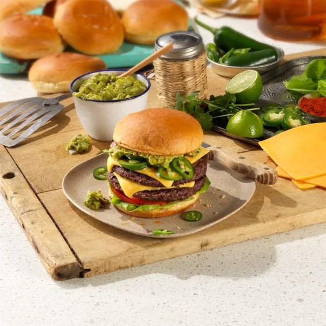 Impossible Cheeseburger with tongs and guacamole on a carving board next to limes