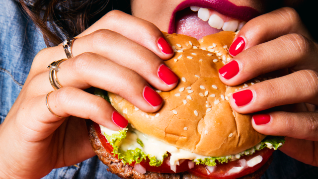 A woman eating an Impossible™ Burger sandwich with lettuce, tomato, onions, and melty cheese.