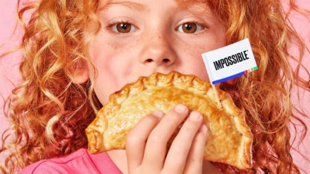 Little girl holding an Impossible Empanada with a flag