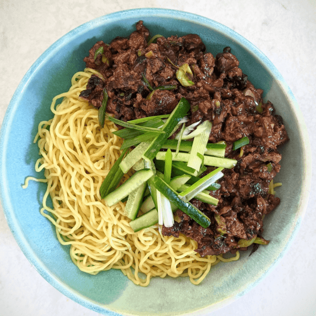 Impossible™ Zha Jiang Mian, a Chinese noodle dish with fresh ramen noodles, savory Impossible™ Burger with miso, soy sauce and scallions, served with crisp cucumber.