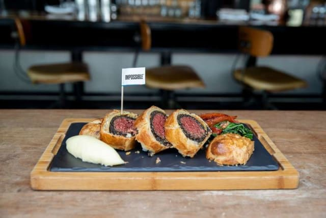 """Impossible™ """"Beef"""" Wellington with an Impossible™ flag on a plate with veggies in a restaurant seating area."""