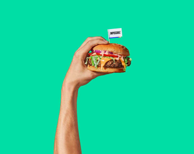 An arm holding up an Impossible™ Burger in triumph