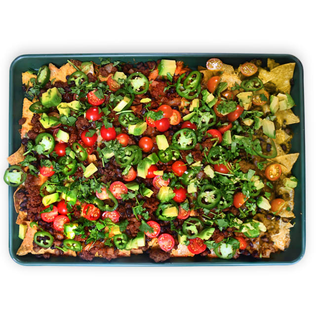 Impossible™ BBQ nachos, piled with Impossible™ Burger, Haven's Kitchen's Tangy BBQ sauce, bright veggies and cilantro