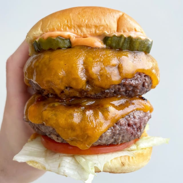 A person holding an Impossible™ Feast Burger with lettuce, tomato, pickles, and melty cheese