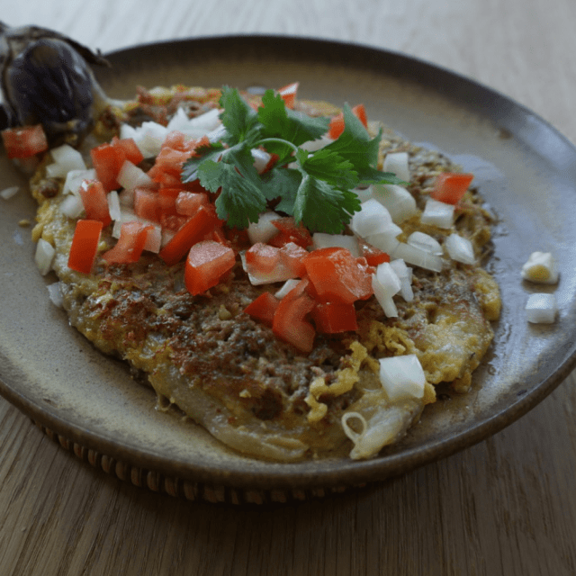 Impossible™ Tortang Talong, traditional Filipino breakfast dish made with eggplant, eggs, and Impossible™ Burger, garnished with tomato, onion, and cilantro.