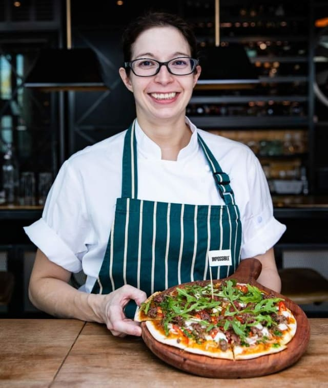 A woman chef smiling while serving Impossible™ Pizza with an Impossible™ flag and veggies in a restaurant.
