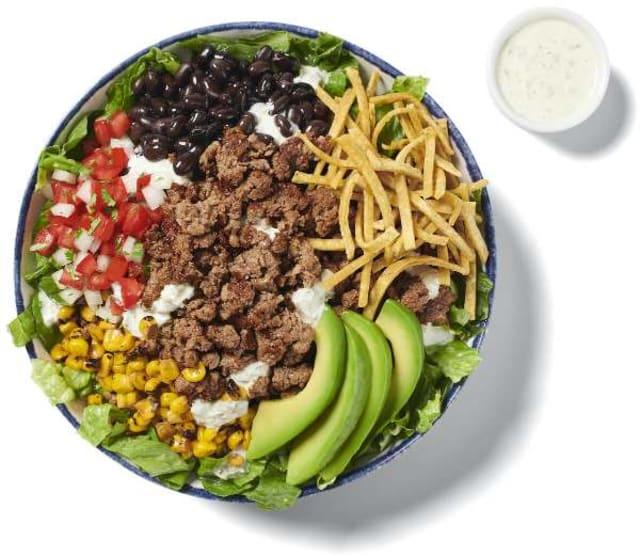 Rubio's Impossible™ Taco Salad in a bowl using Impossible™ Burger, shredded cheese, veggies and a small cup of Ranch dressing