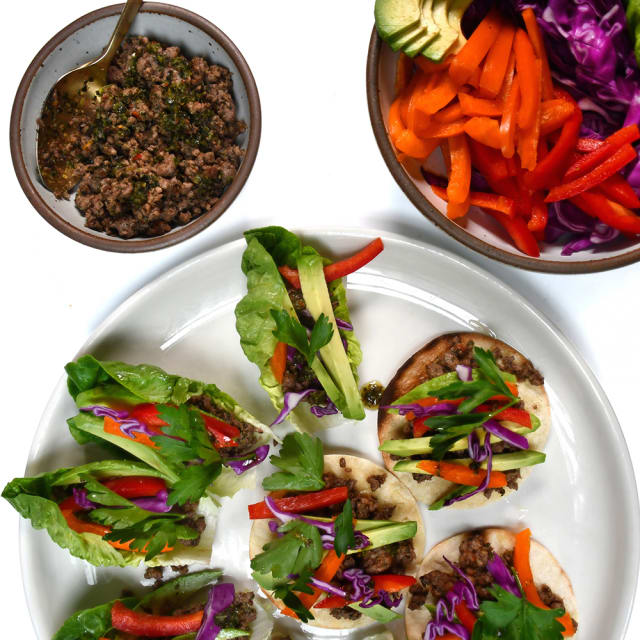 Chimichurri Impossible™ Lettuce Cups made with Haven's Kitchen Herby Chimichurri & Impossible™ Burger, topped with bright veggies and fresh herbs.