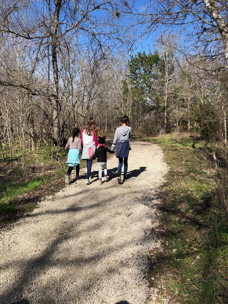 four children hiking on a trail