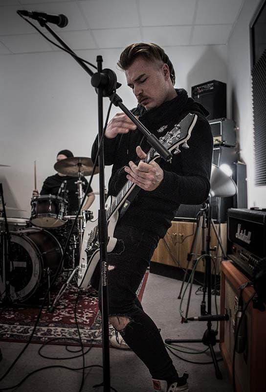 Basti - Musikerfoto - Gitarrist im Hintergrund Schlagzeuger