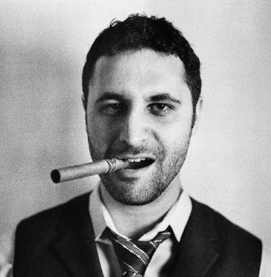 Headshot of John Koht smoking a cigar