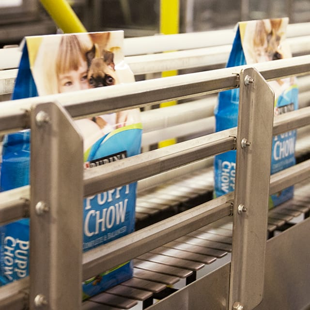Bags of Purina Cat Chow on the assembly line at a factory.