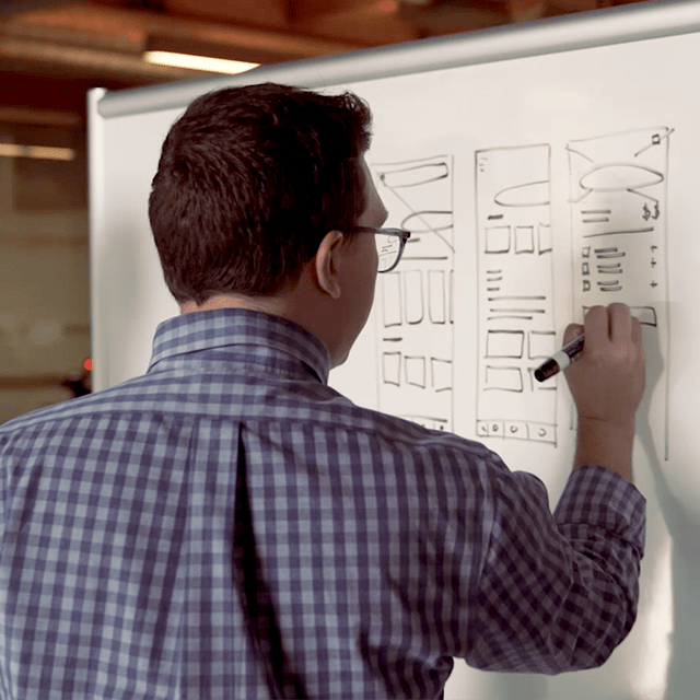Man writing on a board during an ideation session.