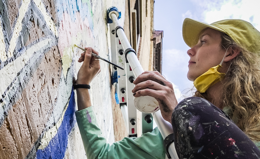 girl on a ladder painting a mural on a brick building with a paint brush