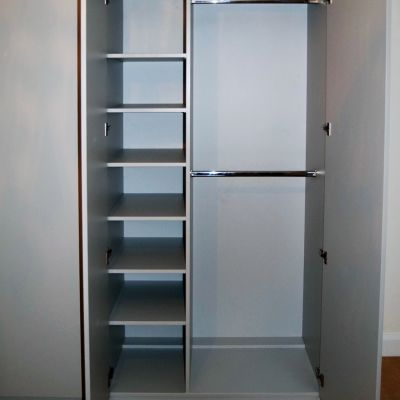 Light grey cabinet with shelves resting on 5mm shelf studs, two hanging rails for double short hanging behind doors hinged with Blum INSERTA Blumotion hinges