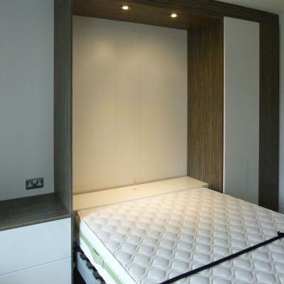 foldaway bed in wardrobe with bedside table