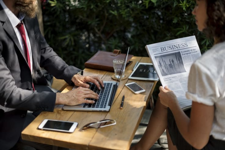 Business people working with laptop reading a newspaper