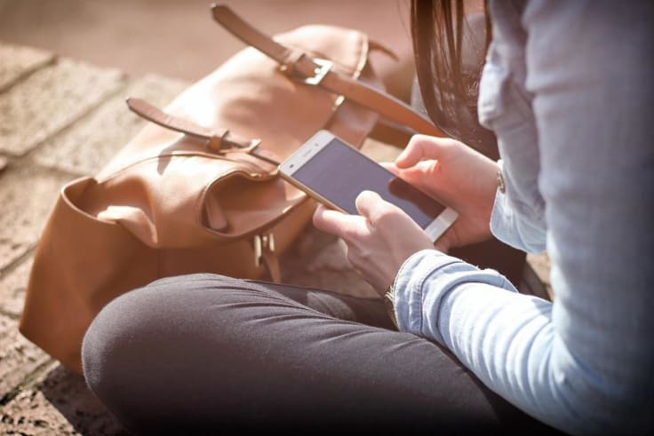 Girl sitting holding a phone texting sms