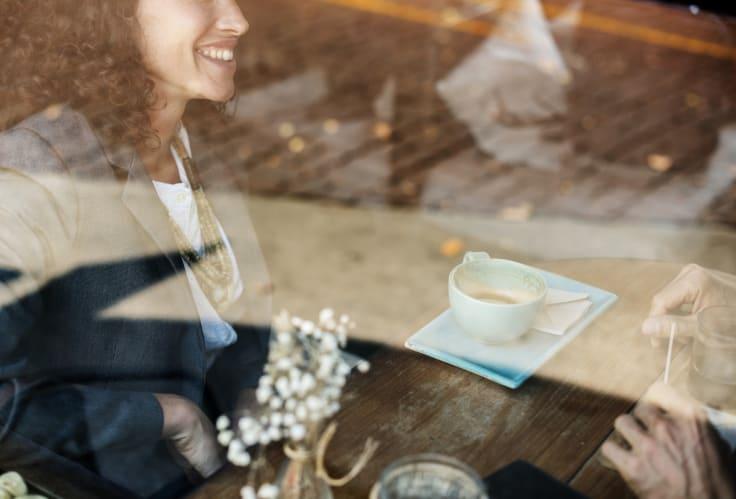 Woman coffee shop behind window smiling