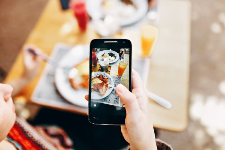 Man holding iphone coffeeshop taking pictures of food