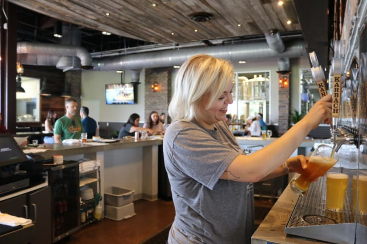 Waitress filling a glass up with beer