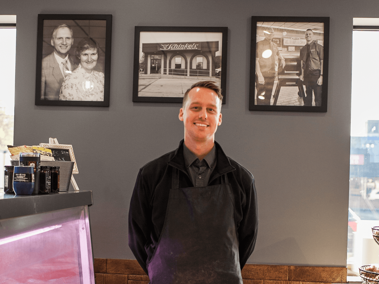 owner standing in front of pictures