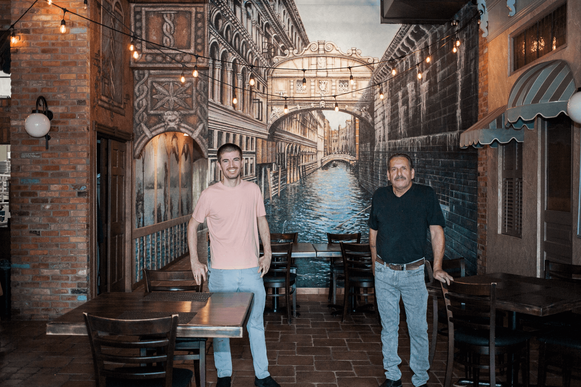 owners standing in front of a mural