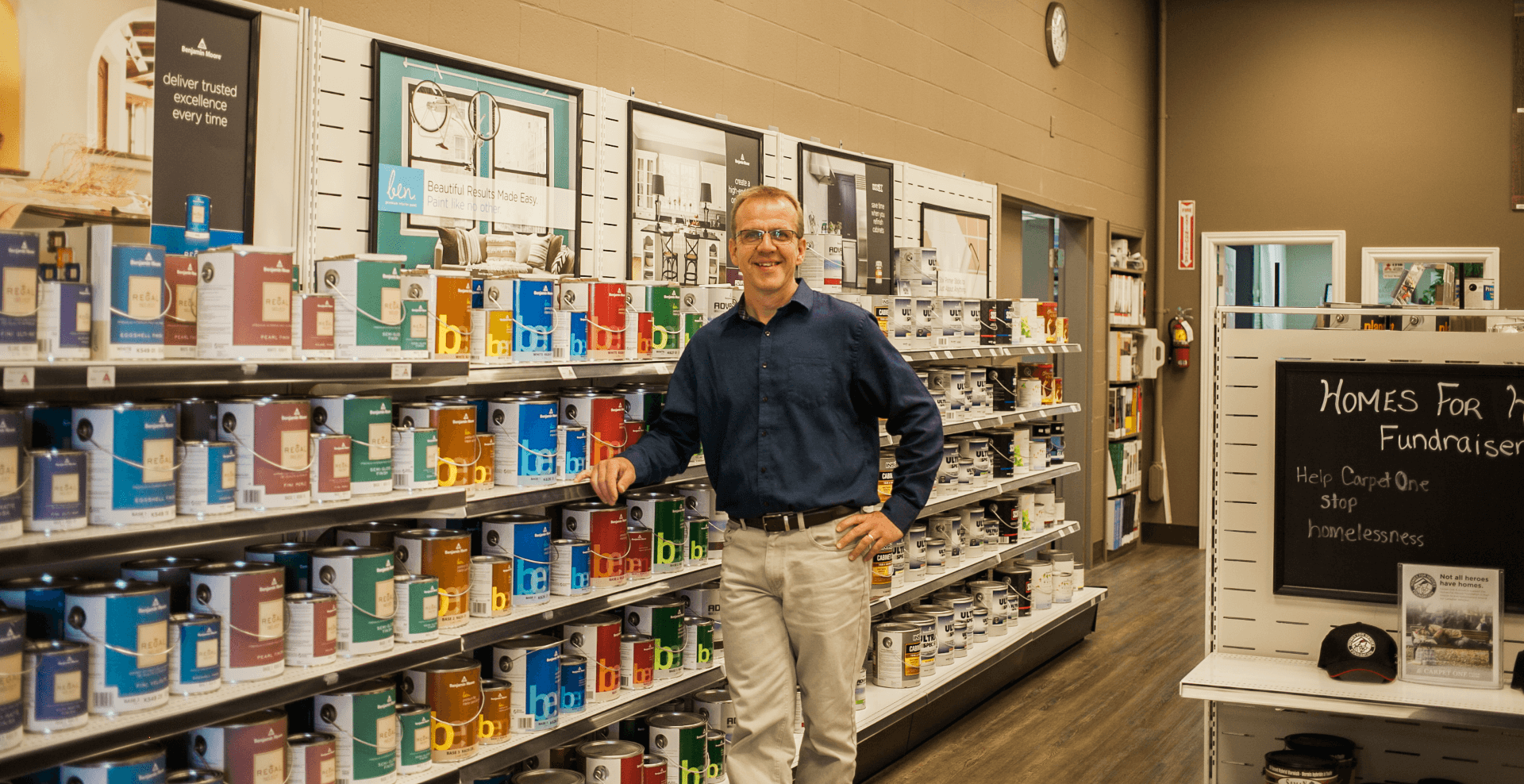 owner standing by paint cans