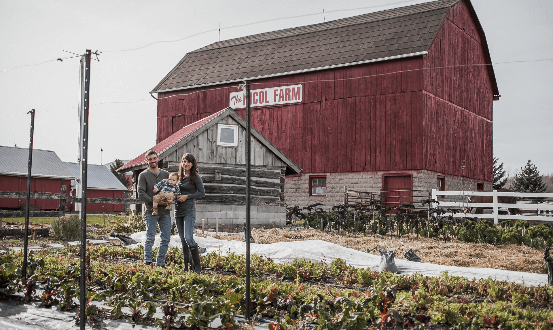 family standing in front of barn
