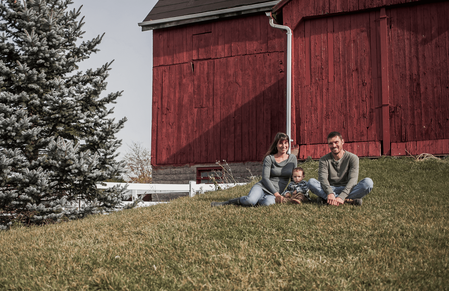 owners with son sitting in front of barn