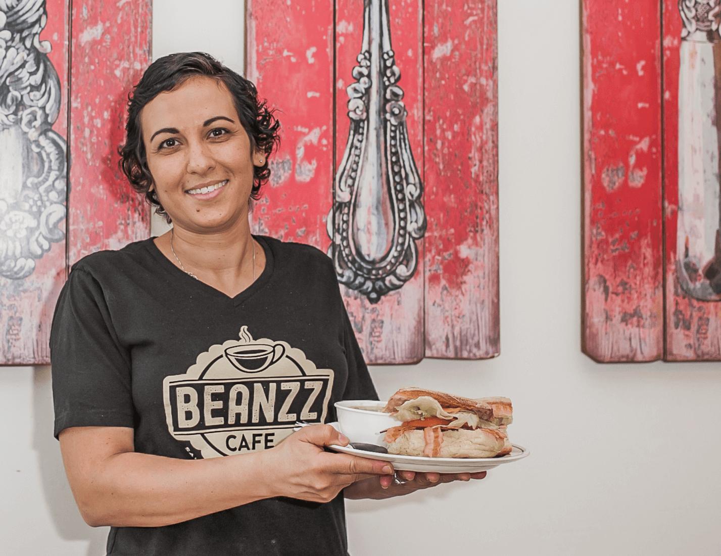cafe owner holding sandwich