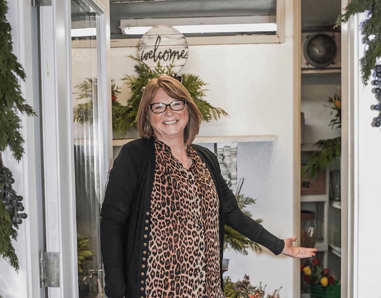 owner in doorway of flower refrigerator