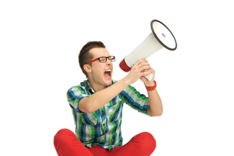 young man sitting and screaming into a megaphone