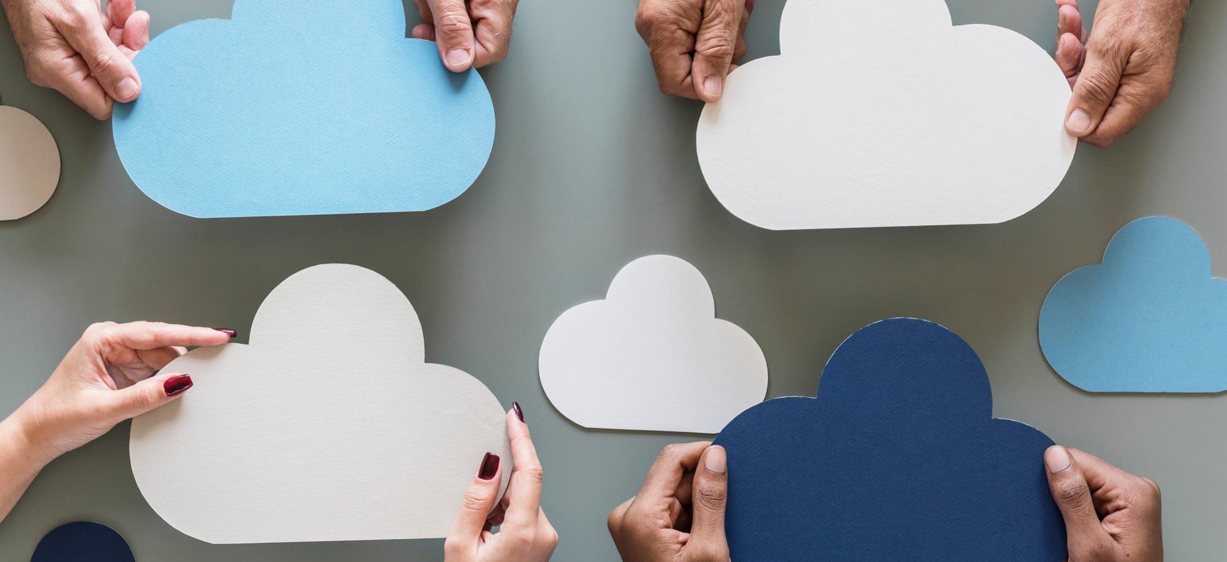 Different people holding paper clouds